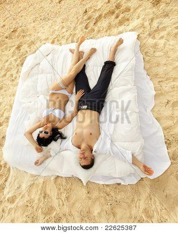 Hermosa joven pareja descansando en la cama en la mañana en la playa