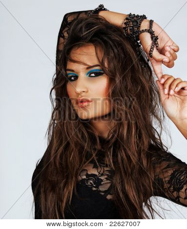 beautiful woman with long messy hair and green eyeshadow wearing lace top with chains on her arms