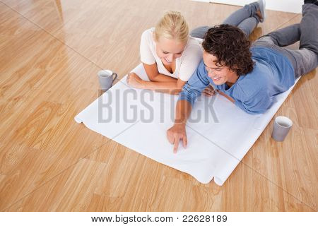 Young man showing a point on a plan to his fiance while lying on the floor