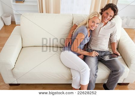 Couple with a tablet computer in their living room