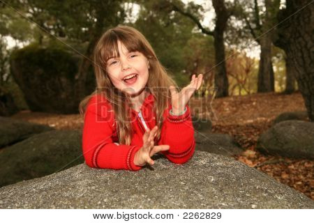 Happy Child Smiling Outdoors On A Rock