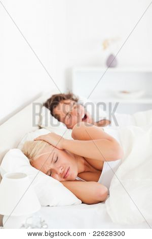 Portrait of an annoyed woman awaken by her boyfriend's snoring in their bedroom