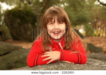 Laughing Child With Arms Crossed Outdoors On A Rock