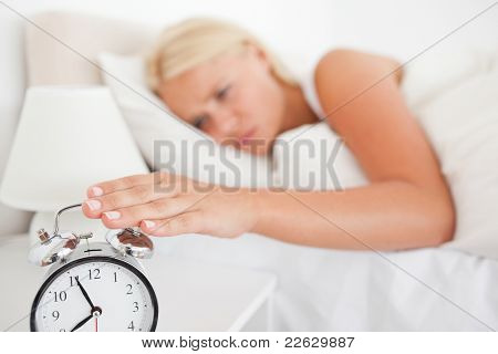 Woman switching off her alarmclock in her bedroom