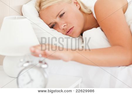 Woman awaken by an alarmclock in her bedroom