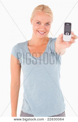 Smiling cute woman showing a phone in a studio
