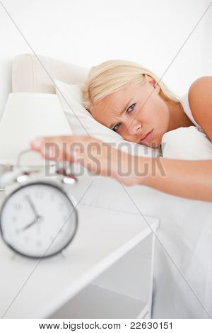 Portrait of a tired woman awaken by an alarmclock in her bedroom
