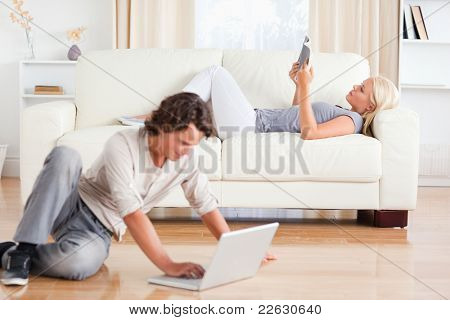 Man using a laptop while his wife is reading a book in their living room