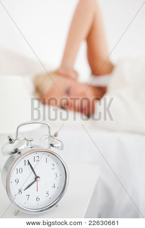 Alarm clock waking up a woman with the camera focus on the clock