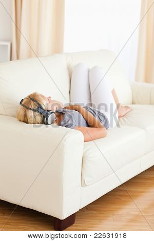 Portrait of a blonde woman with headphones in her living room