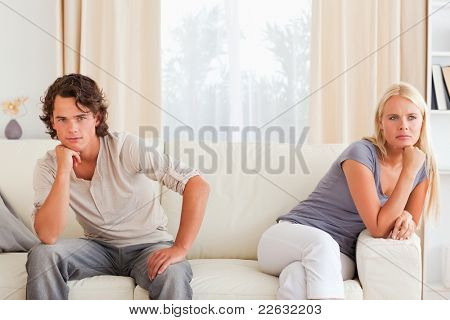 Upset couple sitting on a sofa with their hand on their chin