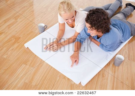Man showing a point on a plan to his girlfriend while lying on the floor
