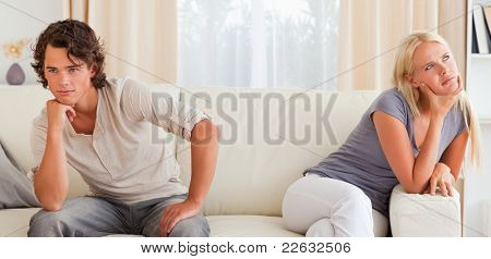 Upset young couple sitting on a couch with their hand on their chin