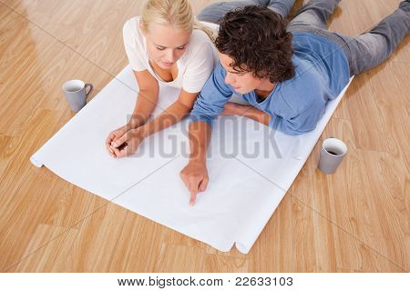 Man showing a point on a plan to his fiance while lying on the floor