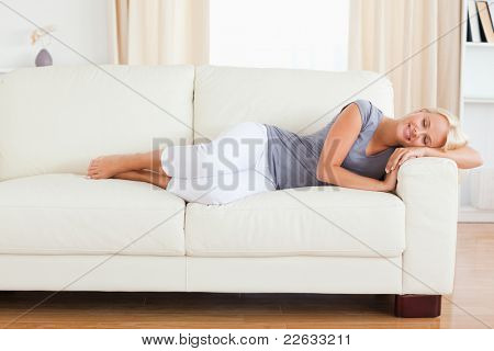 Calm woman resting on a sofa with her eyes closed
