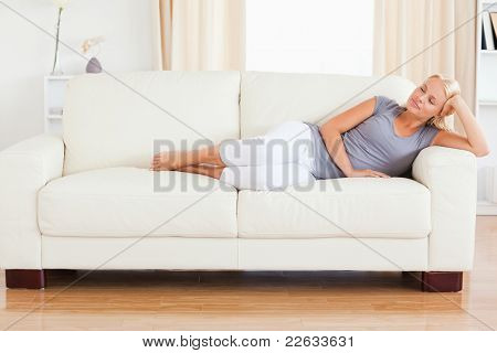 Woman sleeping on a sofa with her eyes closed