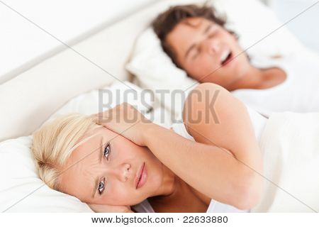Angry woman awaken by her fiance's snoring in their bedroom