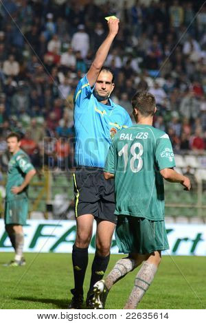 KAPOSVAR, HUNGARY - JULY 30: Adam Nemeth (referee) presents yellow card at a Hungarian National Championship soccer game - Kaposvar (green) vs Videoton (white) on July 30, 2011 in Kaposvar, Hungary.