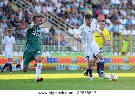 KAPOSVAR, HUNGARY - AUGUST 14: Zoltan Boor (in white 13) in action at a Hungarian National Championship soccer game - Kaposvar (green) vs Ujpest (white) on August 14, 2011 in Kaposvar, Hungary.