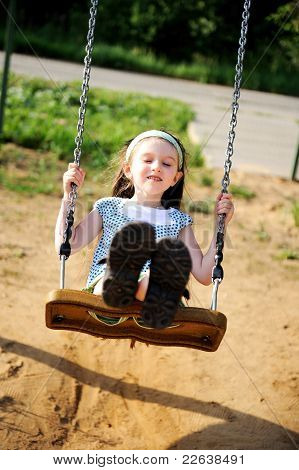 Happy Child Girl Is Swinging In The Playground