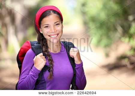Woman hiking in forest. Female hiker smiling happy portrait on beautiful sunny day during a trekking trip. Pretty young Asian woman model outdoors in nature.