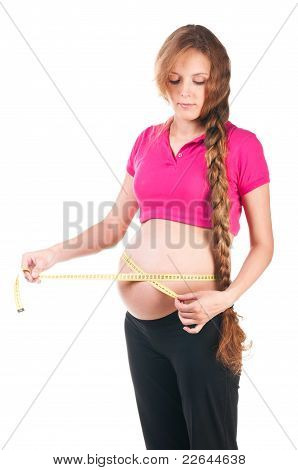 pregnant woman is measuring her stomach