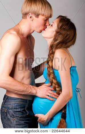 man is kissing pregnant woman