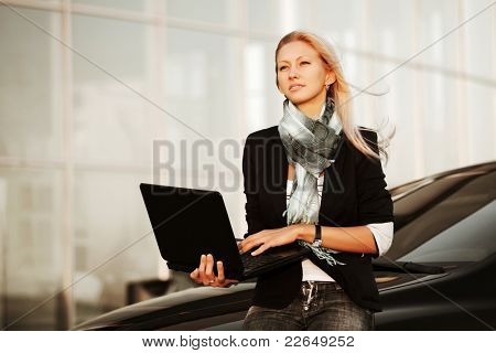 Young woman with laptop sitting on a car