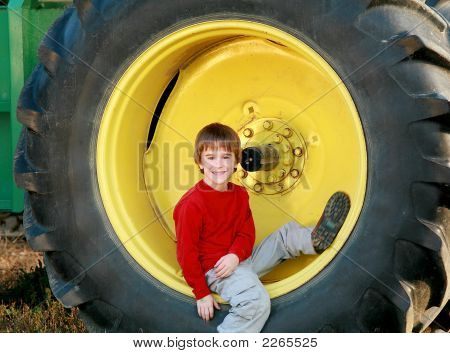 Boy Sitting In Tire