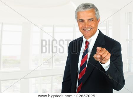 Middle aged businessman in modern office setting pointing at camera. Horizontal Format.