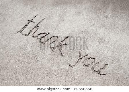 Thank you handwritten in sand on a beach