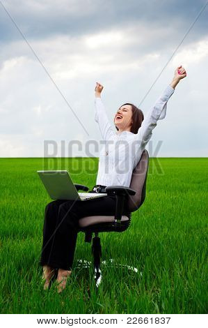 happy businesswoman with computer sitting on chair over green field