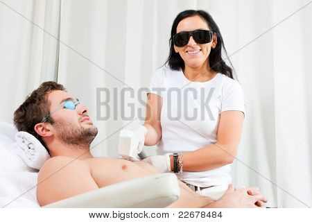 Man receiving waxing in a Day Spa; for protection he and the beautician wear specs