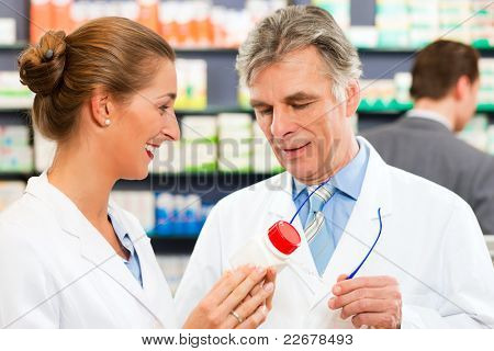 Two pharmacists with pharmaceuticals in hand consulting each other in a pharmacy; a client is standing in the background