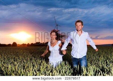 Happy couple is running over grainfield at night; a storm is coming