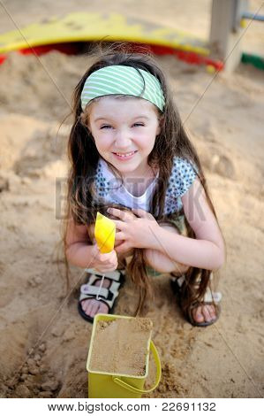 Happy Child Girl Is Playing In A Sandbox