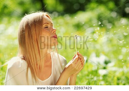 girl blowing on a dandelion lying