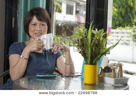 Asian Woman Relaxing In A Cafe