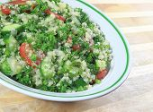 picture of tabouleh  - Quinoa Tabouleh salad in a bowl sitting on a wooden table - JPG