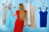Young Blonde Long Hair Woman In Clothes Shop Store Picking Summer Outfit, Dresses Hanging On Clothin poster
