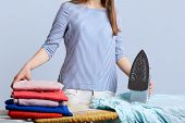 Unrecognizable Female In Blouse Stands At Iron Board Surrounded With Pile Of Laundry, Going To Iron, poster