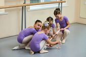 Four Young Ballerinas In Ballet Class. Group Of Young Beautiful Ballet Dancers Having Communication  poster