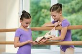Little Ballerina Showing Slippers To Friend. Two Beautiful Ballerinas With Ballet Shoes In Classical poster