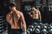 Good Looking Young Man Lifting Dumbbells And Working On His Biceps In Front Of The Mirror Looking On poster