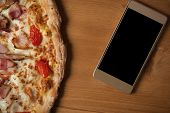 Food Delivery And Online Order Concept. Fresh Italian Pizza And Smartphone On Wooden Table. Place Fo poster