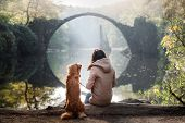 The Girl With The Dog At The Bridge. Nova Scotia Duck Tolling Retriever At The Bridge In The Park poster