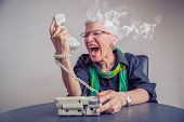 Angry, Enraged Senior Woman Yelling At A Landline Office Phone, Unhappy With Customer Service Provid poster