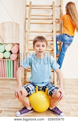 Elementary aged boy sitting on yellow gymnastic ball