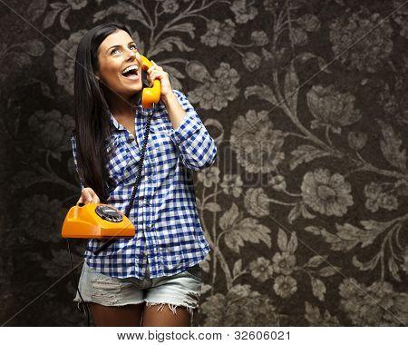 retrato de uma jovem mulher falando no telefone vintage contra uma parede vintage