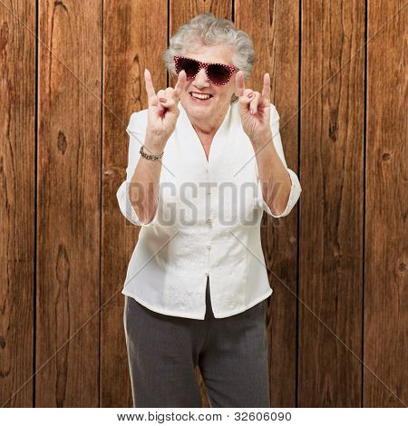 portrait of a happy senior woman doing a rock symbol against a wooden wall